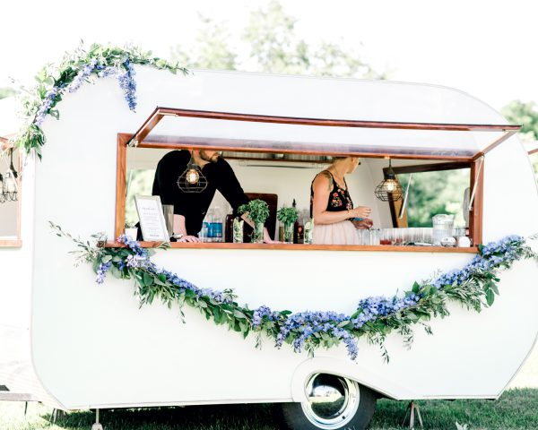 Flower garland-draped bar made out of converted horse trailer at outdoor summer wedding