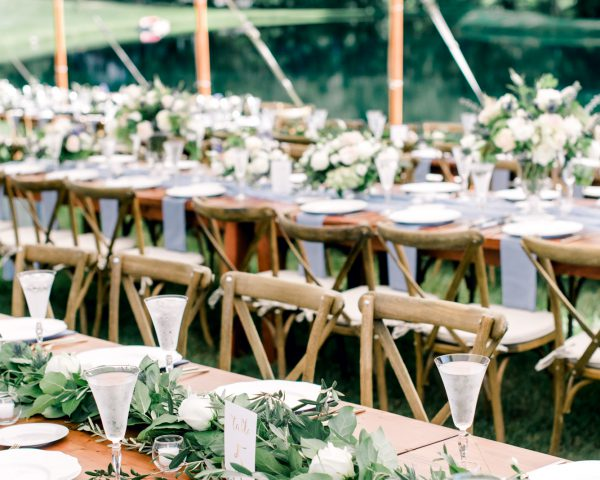 Green garland table runner on wooden farm table under tent