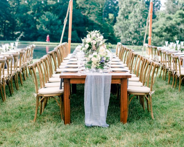 Long wooden farm table with blue accents under sailcloth tent