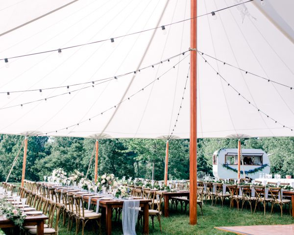 Wedding reception with long wooden farm tables under sailcloth tent