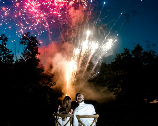 Couple in wooden chairs watching fireworks at their wedding