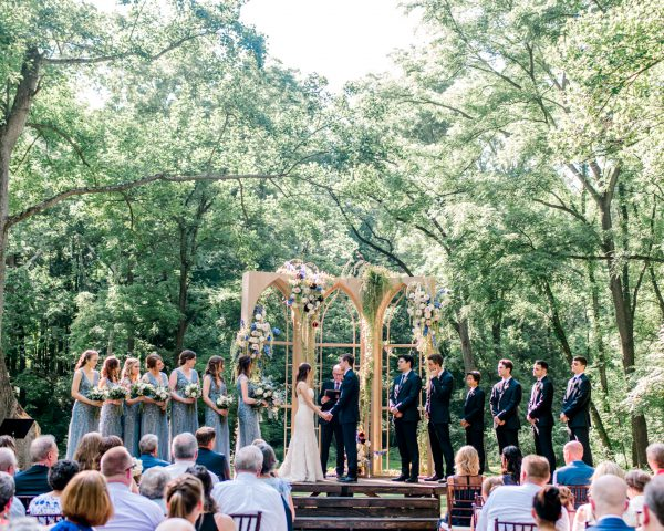 Outdoor wedding ceremony in front of window panel backdrop draped in flowers