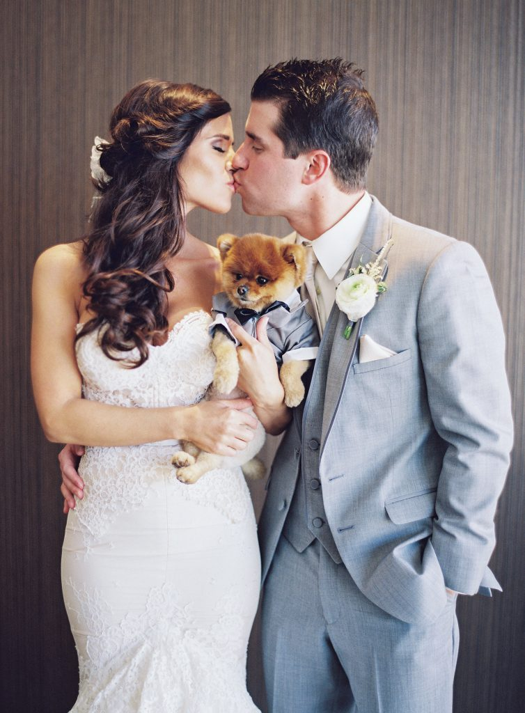 Bride and Groom Kissing with Puppy