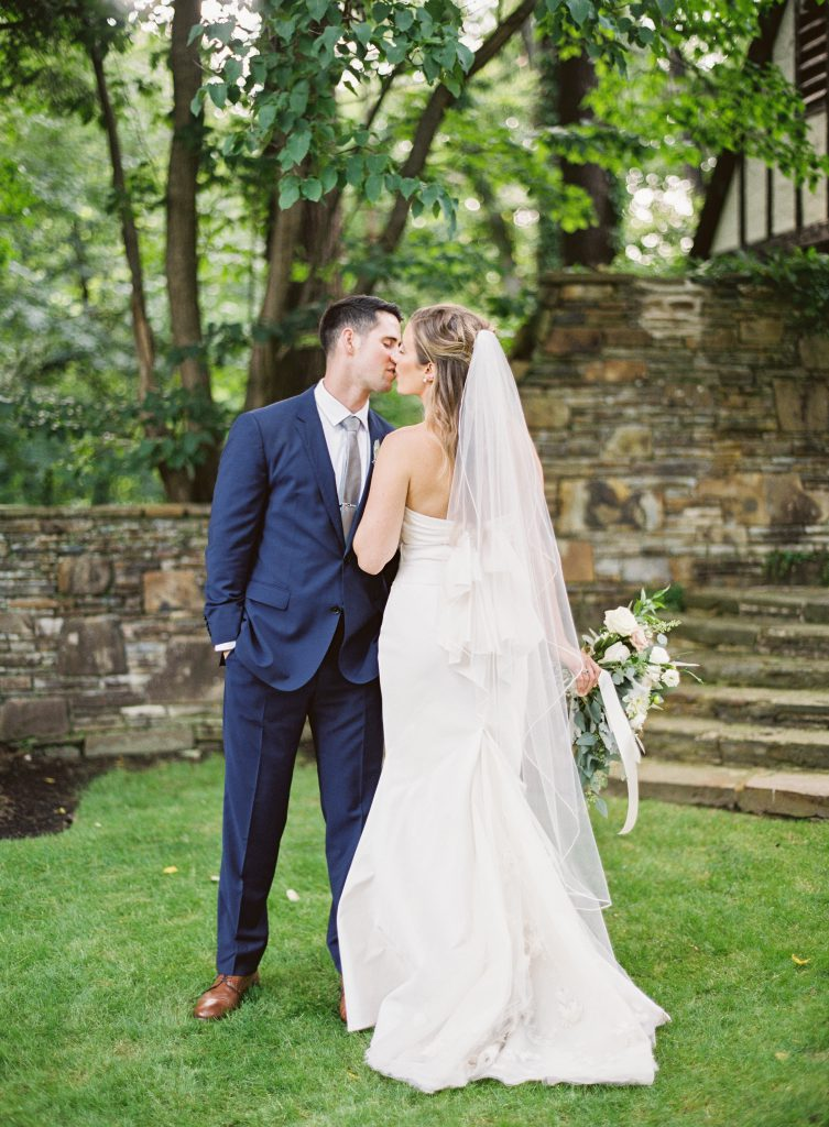 Bride Kissing Groom with Flowers