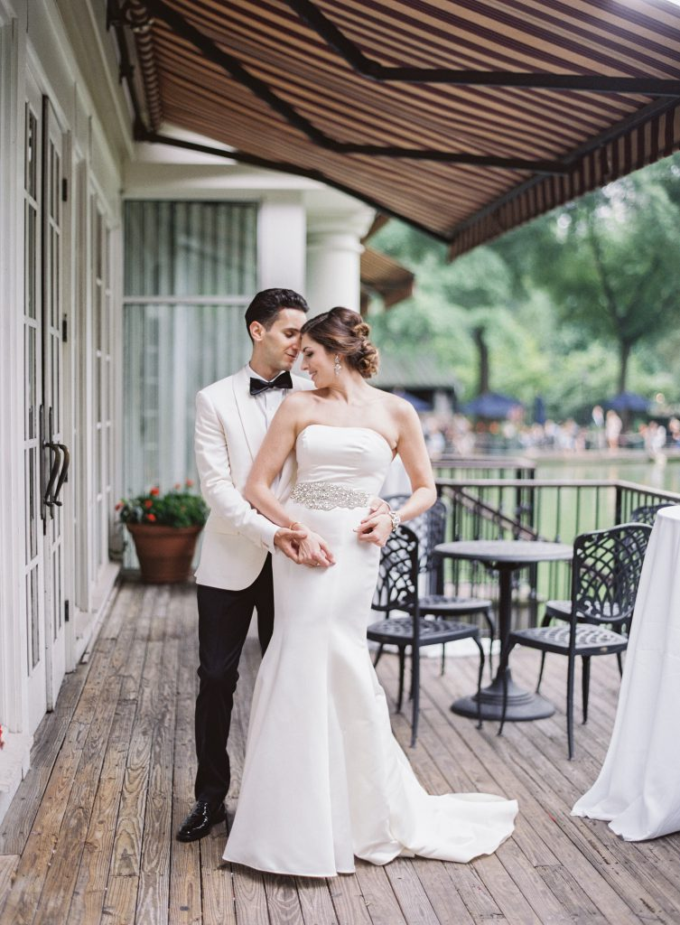 Groom in white tux holds bride
