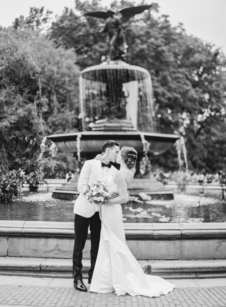 Bride and Groom kissing in front of water fountain