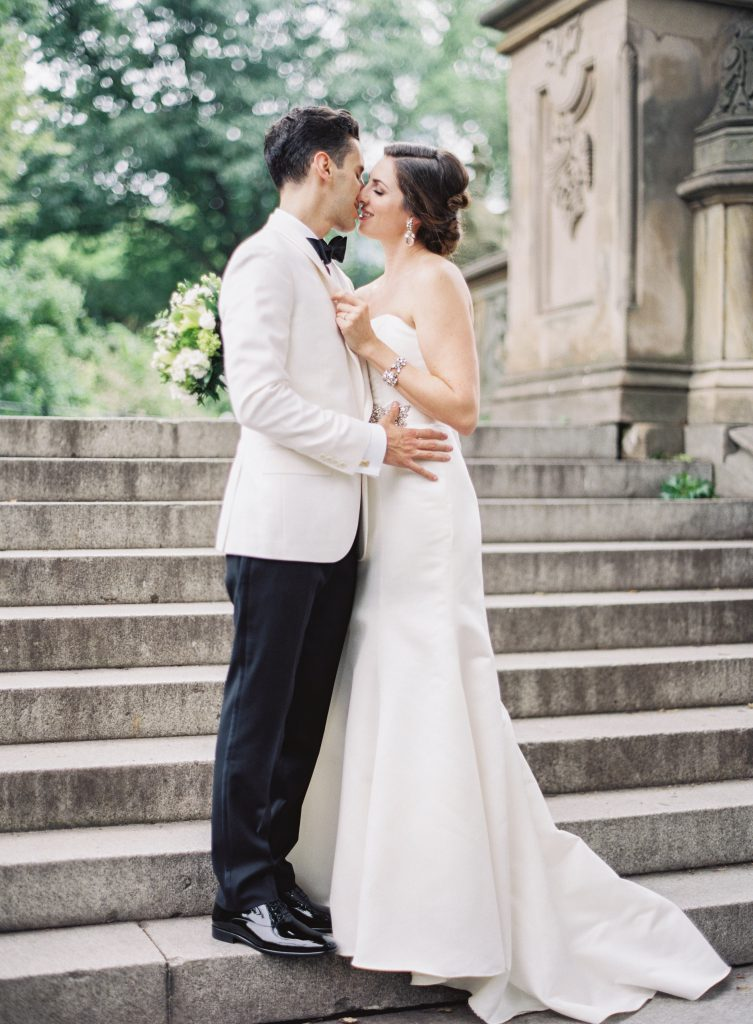 Bride and groom hold each other on stone steps