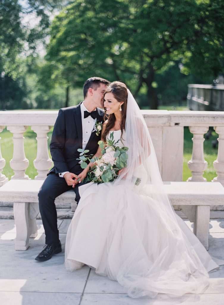 Bride and Groom sitting on bench at Cleveland Museum of Art Wedding