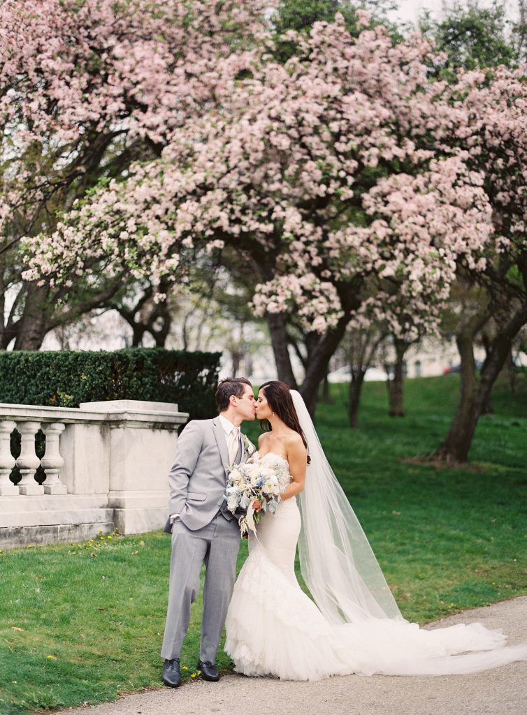 Bride and Groom kiss under cherry blossoms at Cleveland Museum of Art