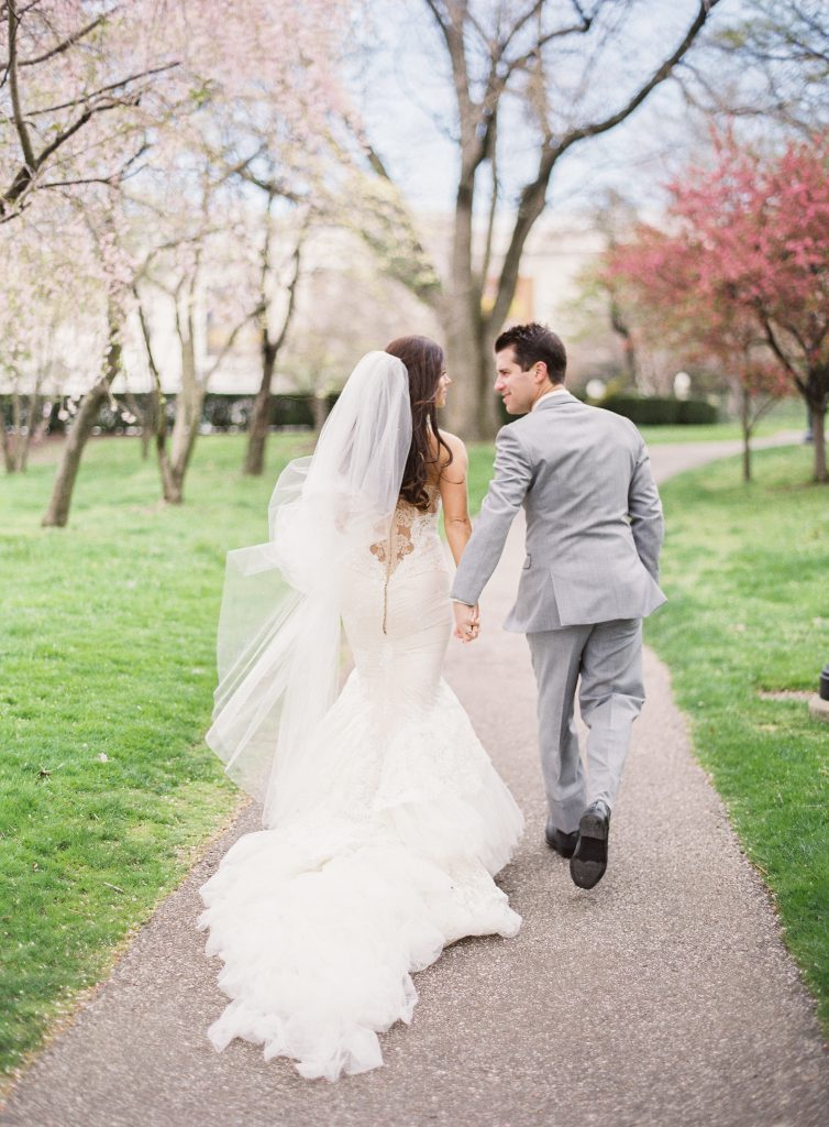 Bride and Groom walk down road at Cleveland Museum of Art Wedding