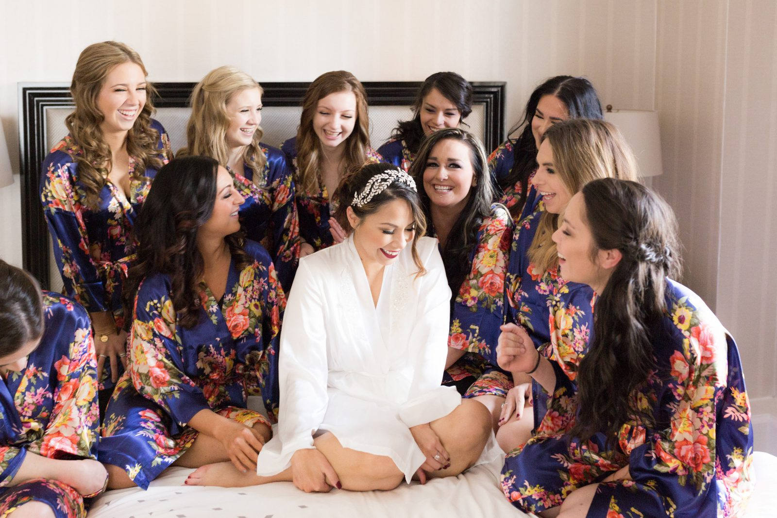 Bride and bridesmaids on bed in coordinating flower robes