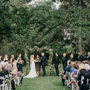 Outdoor ceremony in front of flower arch
