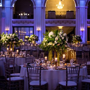 Candlelit tables with large flower centerpieces at Ballroom at the Ben
