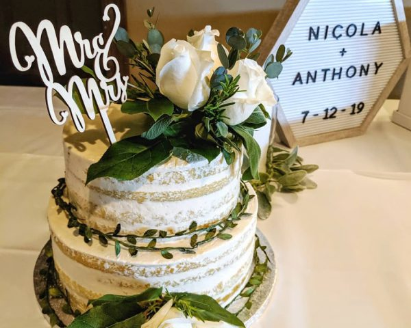 Naked almond vanilla wedding cake with fresh herbs as garnish